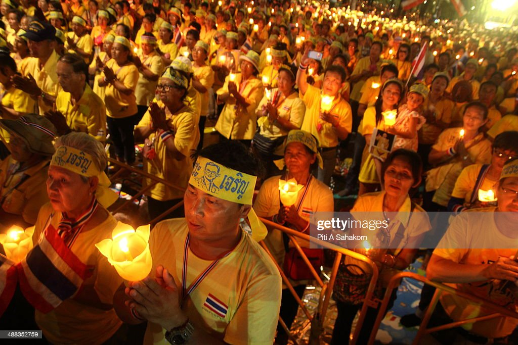 Anti-government protesters hold candles during a ceremony showing their loyalty to King Bhumibol Adulyadej on the 64th anniversary of his Coronation Day. Thailand's revered King Bhumibol Adulyadej made a rare public appearance to mark the 64th anniversary of his coronation. Thailand's Election Commission and the caretaker government agreed to hold new elections on 20 July 2014 after several months of political turmoil and uncertainty while anti-government protesters calling the resignation of caretaker Prime Minister Yingluck Shinawatra and demanding political reforms before any new elections.