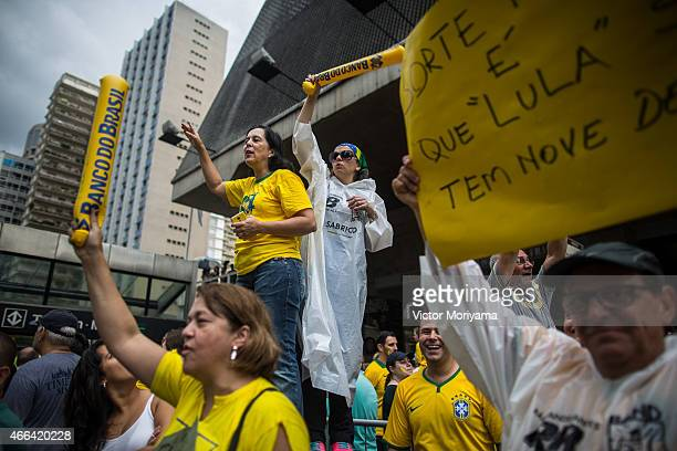 Antigovernment protesters hold signs as they march along Avenida Paulista on March 15 2015 in Sao Paulo Brazil Protests across the country were held...
