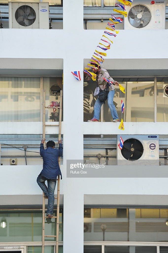 Anti-government protesters make preparations to mark the 86th birthday of Thai King Bhumibol Adulyadej by erecting royal and Thai national flags between buildings in the occupied Ministry of Finance compound on December 4, 2013 in Bangkok, Thailand. Protesters have occupied the ministry for nine days. Tensions have eased in the run up to the king's birthday on Thursday, with protesters declaring a temporary truce in their campaign to topple the government.