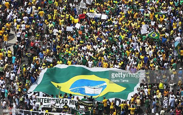 Antigovernment protesters march carrying a Brazilian flag along Copacabana beach on March 15 2015 in Rio de Janeiro Brazil Protests across the...