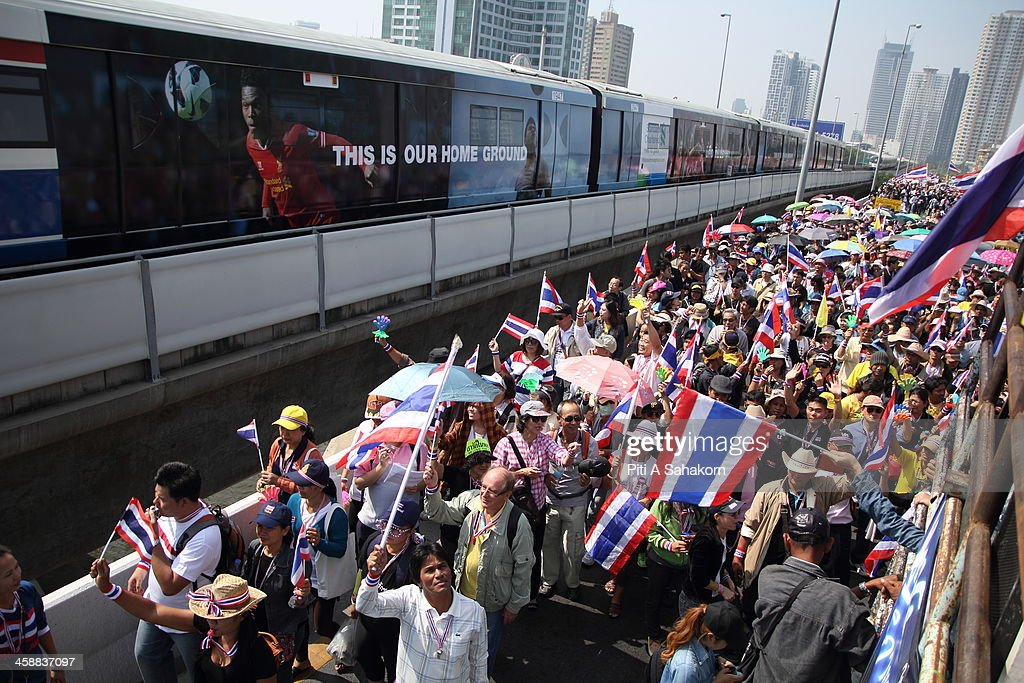 Anti-government protesters march near the BTS railway that crosses the Taksin Bridge during a rally in Bangkok. More than one million anti-government protesters massed ahead of a major rally aimed at toppling the Prime Minister, paralysing parts of central Bangkok. The Election Commission (EC) has expressed concern over the mass anti-government rallies beginning today, fearing they could prevent the first day of election candidate registration on Monday. The Democrat Party said it would boycott February's general election, deepening a political crisis as protesters called for another major rally to step up efforts to oust the government and force political reforms.