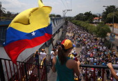 Antigovernment protesters march through the streets on March 8 2014 in San Cristobal the capital of Tachira state Venezuela Shortage of such products...