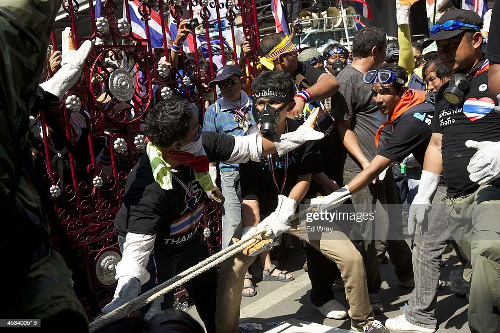 Anti-government protesters pull over a barricade in front of the central police headquarters during a demonstration on December 4, 2013 in Bangkok, Thailand. The protesters continued their demonstration, though in keeping with the relative calm after several days of violent clashes with police, there was no violence.