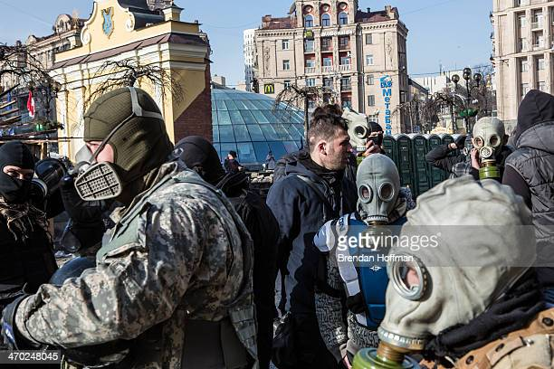 Antigovernment protesters put on gas masks near the perimeter of Independence Square known as Maidan on February 19 2014 in Kiev Ukraine After...