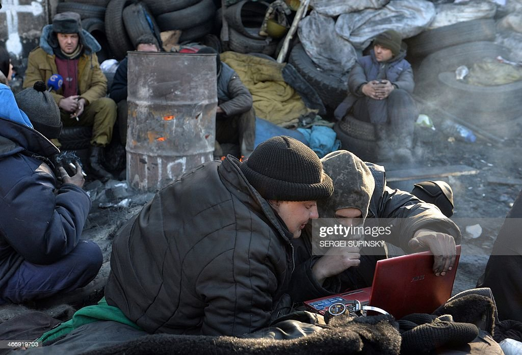 Anti-government protesters read the last news on internet at a barricade in Kiev on February 5, 2014. Ukraine's parliament will try again on February 5 to agree on curbing the presidency's powers, while the EU's foreign policy chief meets embattled President Viktor Yanukovych to press for a resolution of the political crisis. The crisis has sparked tensions between the West, which is considering sanctions against Ukrainian officials, and Russia, which has accused the EU and US of interference in the former Soviet republic.