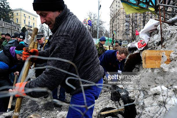Antigovernment protesters rebuild a barricade as rising temperatures melt the snow previously used to build it close to Independence Square on...