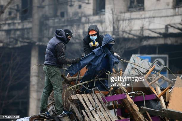 Antigovernment protesters rebuild barricades following continued clashes with police in Independence square despite a truce agreed between the...