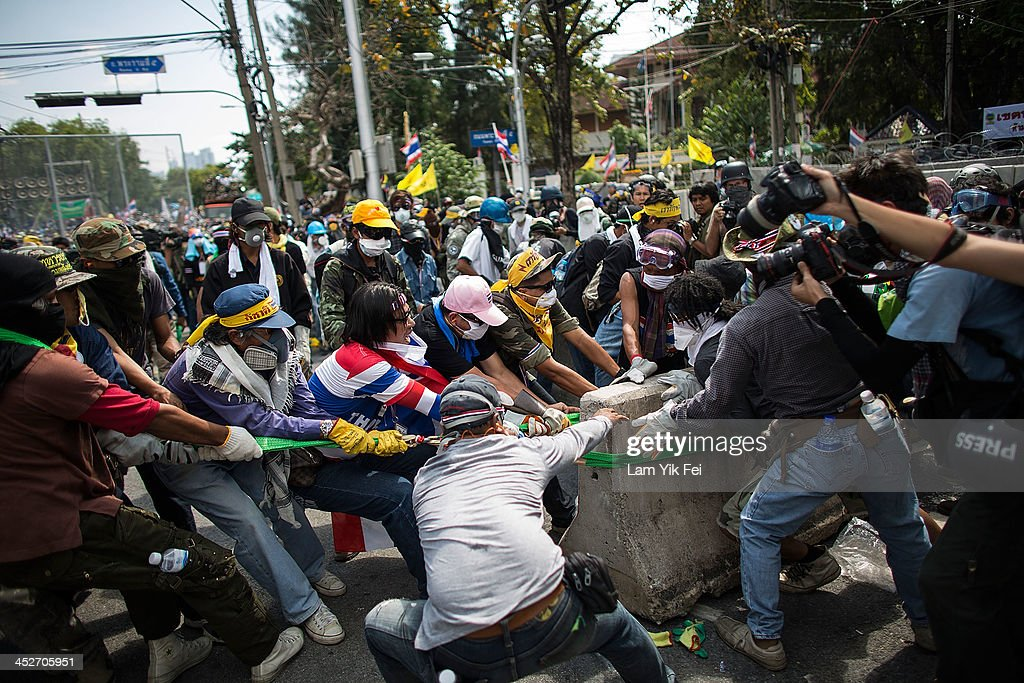 Anti-government protesters remove part of a barricade as they attempt to occupy the government house on December 1, 2013 in Bangkok, Thailand. Anti-government protesters in Bangkok say they plan to occupy the government house and the zoo, demonstrators calling on the government to step down have marched on ministries and government bodies in an attempt to shut them down.