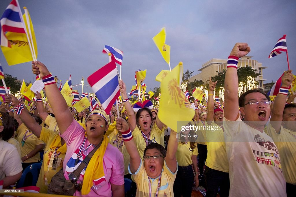 Anti-Government protesters shout after singing the Royal anthem during a celebration of the Thai King Bhumibol Adulyadej' 86th birthday, at the democracy monument which protesters have been occupying on December 5, 2013 in Bangkok, Thailand. The tension between police and anti-government protesters has calmed as the protesters have temporarily agreed to halt their activities to pay respect to the King on his birthday.