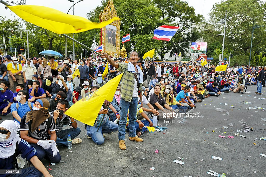 Anti-government protesters sit on the ground to face riot police during a large anti government protest on November 24, 2012 in Bangkok, Thailand. The Siam Pitak group, which sponsored the protest, cited alleged government corruption and anti-monarchist elements within the ruling party as grounds for the protest. Police used tear gas and baton charges againt protesters.