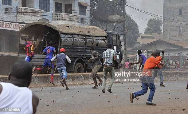 Antigovernment protesters throw stones at an armoured truck of the security forces in Conakry on May 4 2015 More than 20 people were wounded on May 4...