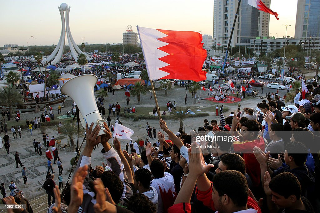 Antigovernment protesters wave flags and demonstrate at the Pearl roundabout on February 20 2011 in Manama Bahrain Protesters filled the square for...