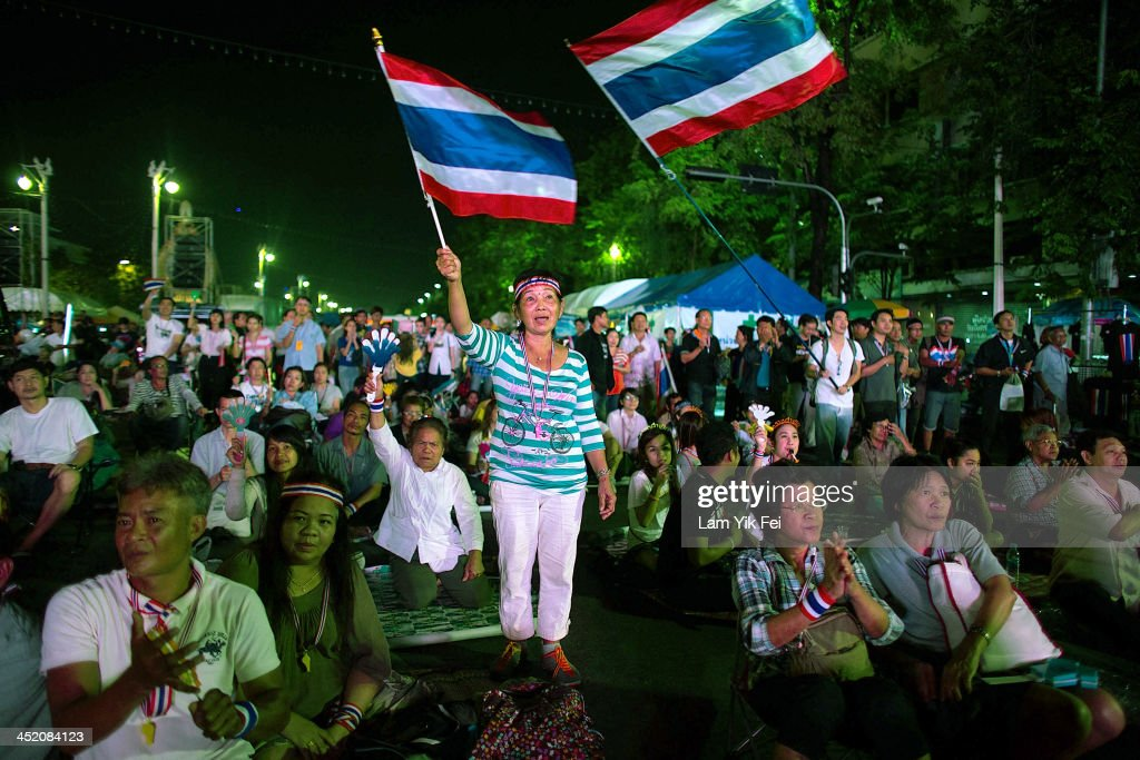 Anti-government protesters wave national flags during a rally at Democracy Monument on November 26, 2013 in Bangkok, Thailand. The Prime Minister of Thailand, Yingluck Shinawatra, has announced the use of a special security law to counter demonstrators who stormed into government departments during a day of mass protests across Bangkok.