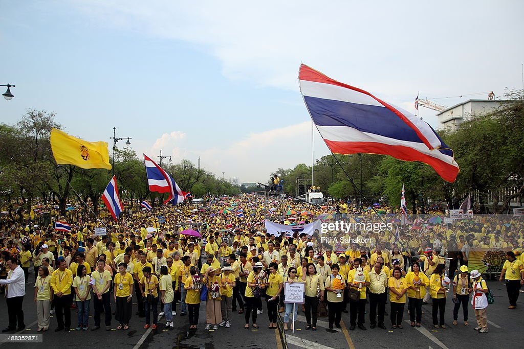 Anti-government protesters wave Thai national flags during a rally showing their loyalty to King Bhumibol Adulyadej on the 64th anniversary of his Coronation Day. Thailand's revered King Bhumibol Adulyadej made a rare public appearance to mark the 64th anniversary of his coronation. Thailand's Election Commission and the caretaker government agreed to hold new elections on 20 July 2014 after several months of political turmoil and uncertainty while anti-government protesters calling the resignation of caretaker Prime Minister Yingluck Shinawatra and demanding political reforms before any new elections.