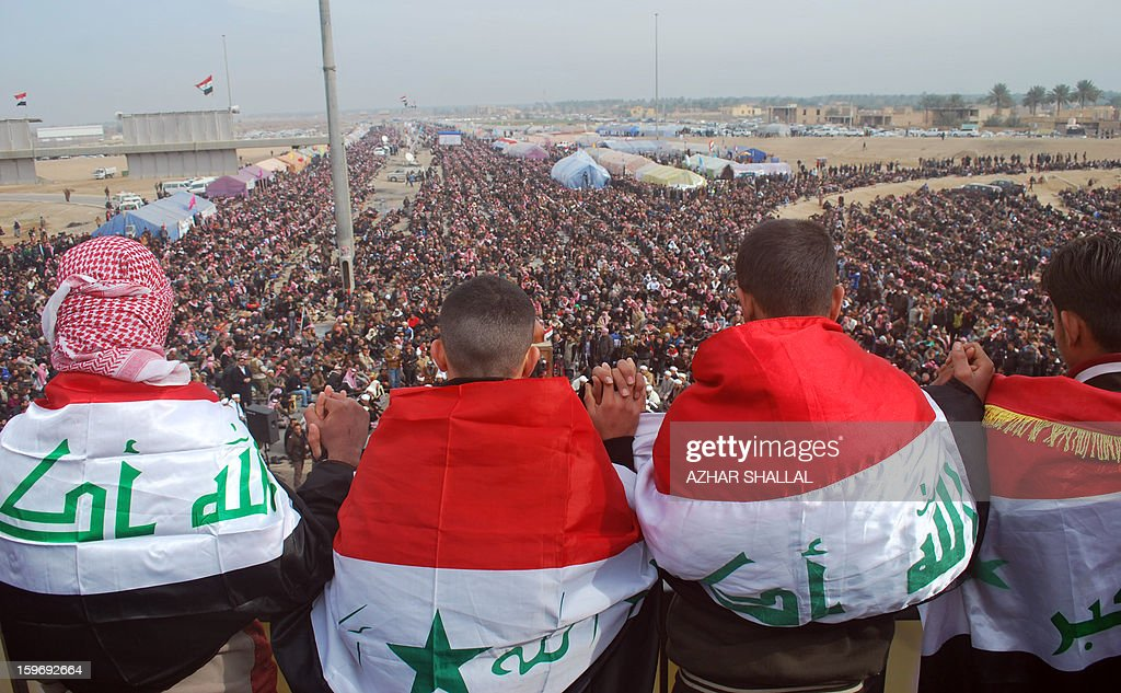 Anti-government protesters, wrapped in national flags, take part in a rally held after the weekly Fridy prayer in the western Iraqi city of Ramadi on January 18, 2013. Thousands of Sunni Muslims took to the streets of the capital Baghdad and other parts of Iraq on to decry the alleged targeting of their minority, in rallies hardening opposition to the country's Shiite leader. AFP PHOTO/AZHAR SHALLAL