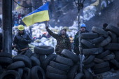 Antigovernment protestors look towards police lines from a wall of tyres on Grushevskogo Street on January 27 2014 in Kiev Ukraine Unrest is...