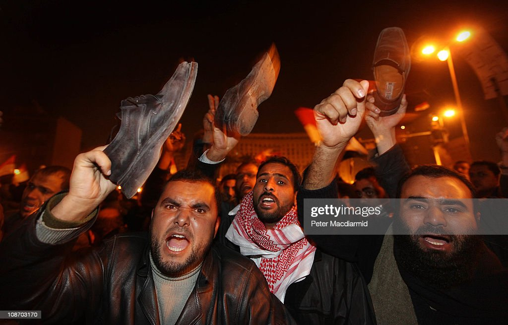 Anti-government protestors waves their shoes, in a gesture of anger, after President Hosni Mubarak announces that he will not seek re-election on February 1, 2011 in Cairo, Egypt. Protests in Egypt continued with the largest gathering yet, with many tens of thousands assembling in central Cairo, demanding the ouster of Egyptian President Hosni Mubarak. The Egyptian army has said it will not fire on protestors as they gather in large numbers in central Cairo.