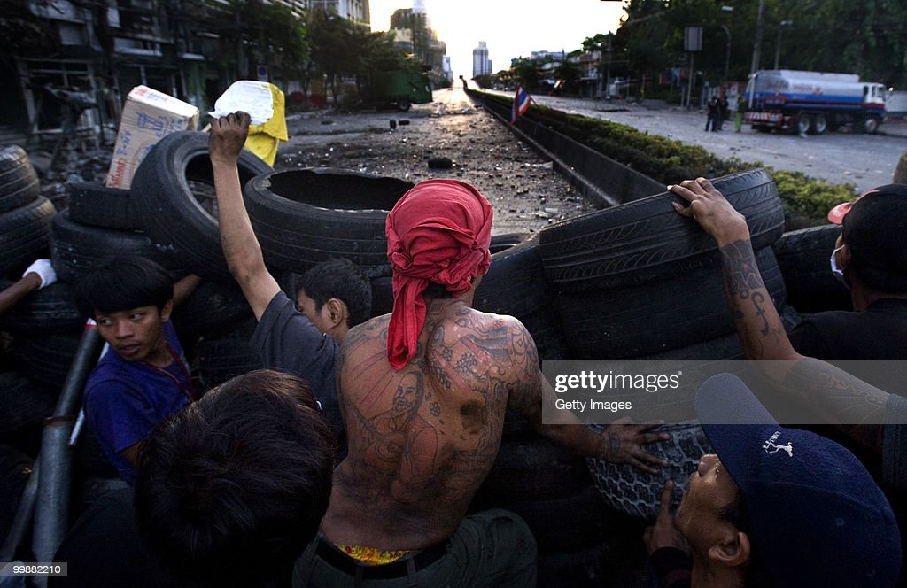 Anti-government red shirt protesters look over a barricade towards a military position as their fellow protesters attempt to return an oil truck to a nearby petrol station on May 18, 2010 in Bangkok, Thailand. Protesters have clashed with military forces for five consecutive day in Bangkok after the government launched an operation to disperse anti-government protesters who have closed parts of the city for more than two months. Despite calls from the United Nations for both sides to begin talks, anti-government protesters in Bangkok have defied orders to leave their fortified camp, with 37 people having died and more than 260 injured since the military began its crackdown.