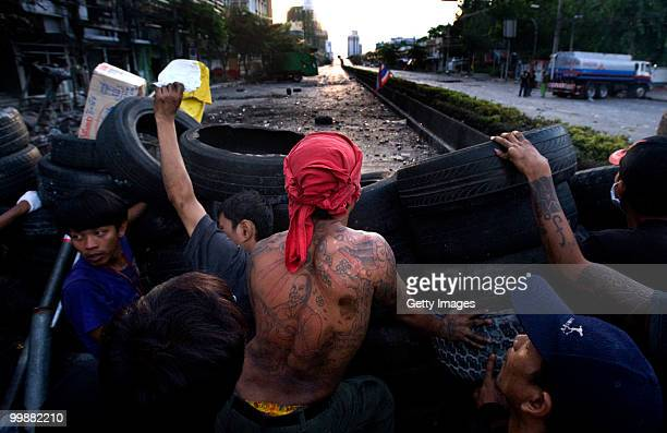 Antigovernment red shirt protesters look over a barricade towards a military position as their fellow protesters attempt to return an oil truck to a...