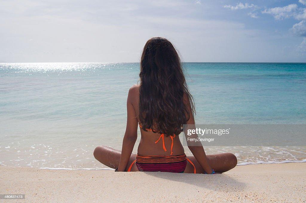 Antigua and Barbuda, Antigua, Rear view of girl sitting on Darkwood beach