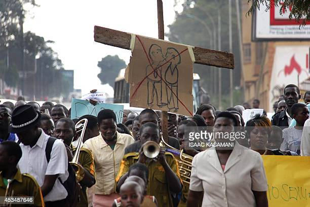 AntiHomosexual activists march on the streets of Kampala carrying placards on August 11 2014 to demonstrate against the recently annulled AntiGay law...