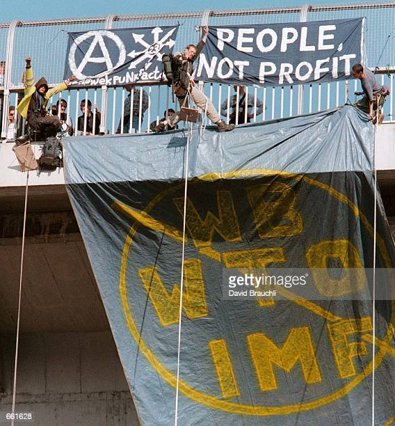 AntiIMF WTO and World Bank protesters shout and wave after unfurling a banner against the IMF WTO and World Bank off the Nusle Bridge leading to the...