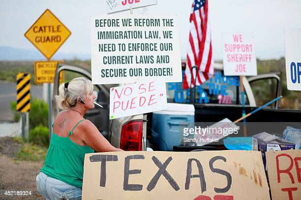 Antiimmigration activist Barb Heller sets up signs on her truck during a protest along Mt Lemmon Road in anticipation of buses carrying illegal...