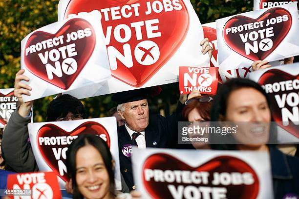 Antiindependence Better Together campaigners hold placards reading 'Protects Jobs Vote No' during a demonstration in Edinburgh UK on Tuesday Sept 16...