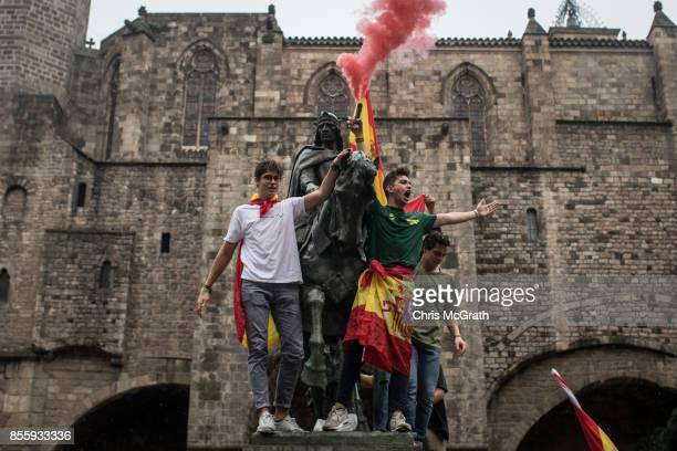 Antiindependence demonstrators light a flare atop a statue during a march in protest against the independence referendum on September 29 2017 in...