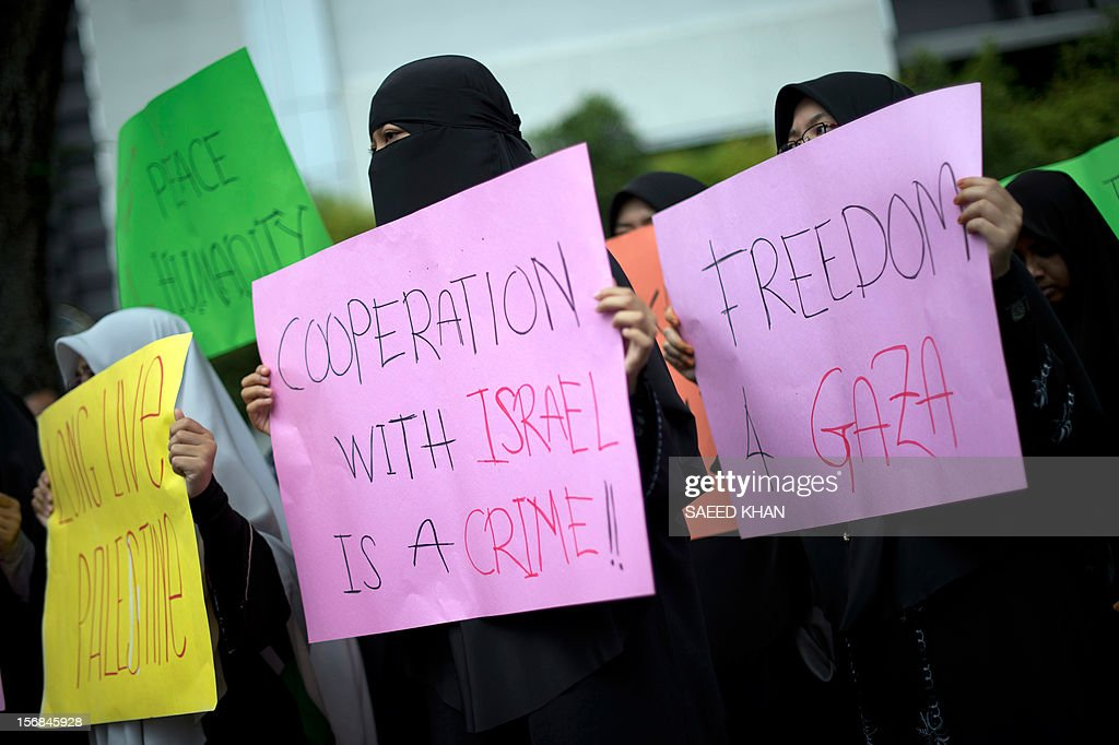 Anti-Israel protesters hold up placards as a group marches towards the US embassy during a protest in Kuala Lumpur on November 23, 2012. Dozens of students after offering their Friday prayers marched towards the US embassy while holding placards and banners to condemn Israel military aggression in Gaza and demanded the US be sincere in its efforts in the crisis. AFP PHOTO / Saeed KHAN