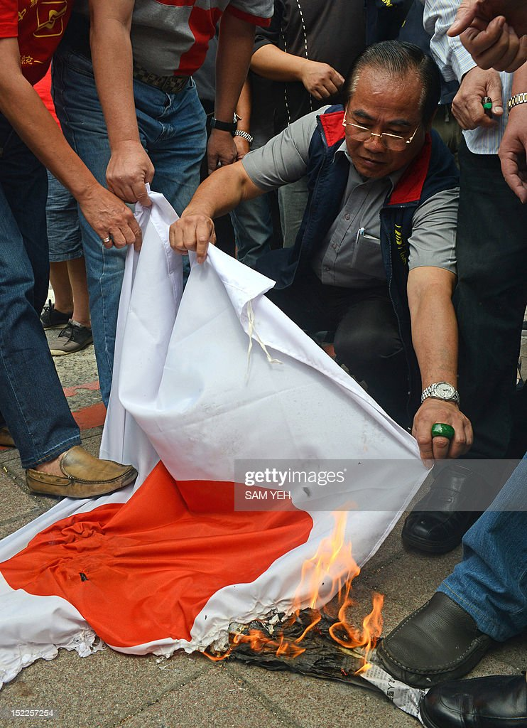 Anti-Japan activists burn a Japanese flag during a protest in front of the parliament building in Taipei over a group of disputed islands, known as the Diaoyu islands in Chinese or the Senkaku islands in Japanese, on September 18, 2012. A group of Taiwanese fishermen are planning to sail this week to the disputed archipelago in the East China Sea at the centre of a territorial row among Taiwan, China and Japan, a politician said. AFP PHOTO / Sam Yeh