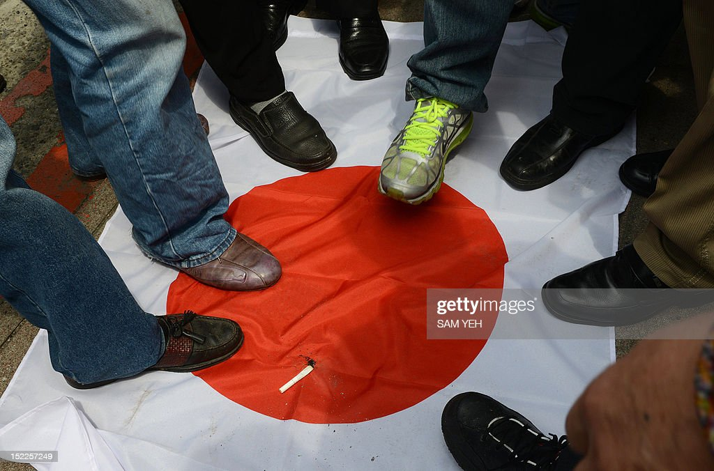 Anti-Japan activists step on a Japanese flag during a protest in front of the parliament building in Taipei to demand the Taiwan government to cooperate with China against Japan over a group of disputed islands, known as the Diaoyu islands in Chinese or the Senkaku islands in Japanese, on September 18, 2012. A group of Taiwanese fishermen are planning to sail this week to the disputed archipelago in the East China Sea at the centre of a territorial row among Taiwan, China and Japan, a politician said. AFP PHOTO / Sam Yeh