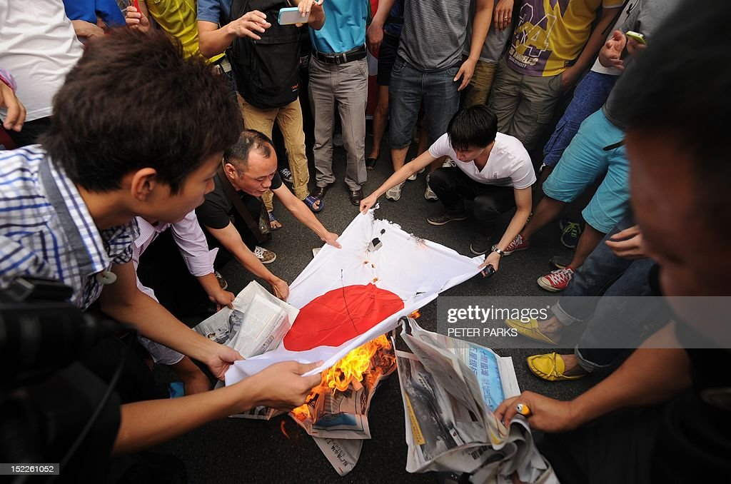 AntiJapan protesters burn a Japanese national flag during a protest over the Diaoyu islands issue known as the Senkaku islands in Japan in the...