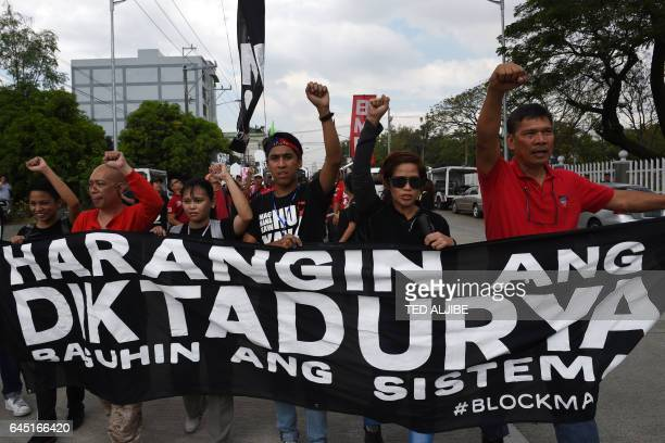 AntiMarcos protesters raise clenched fists and carrying a banner that reads 'Block dictatorship' during a protest in front of the heroes' cemetery in...