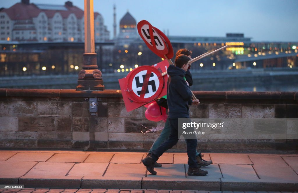 Anti-neo-Nazi activists carry signs showing smarked through swastikas before the creation of a human chain in the city center as a statement against neo-Nazis on the 69th anniversary of the World War II firebombing of the city by the Allies on February 13, 2014 in Dresden, Germany. Neo-Nazis from across Germany have used the anniversary to parade in Dresden in recent years, though a strong, local grass movement against them has prevented their marches and this year led to the cancellation of a neo-Nazi gathering.