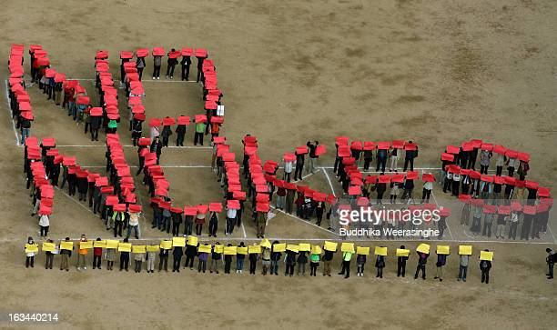 Antinuclear activists gather together and display a 'No Nukes' sign during an antinucler protest on March 10 2013 in Kobe Japan Japan to mark the...