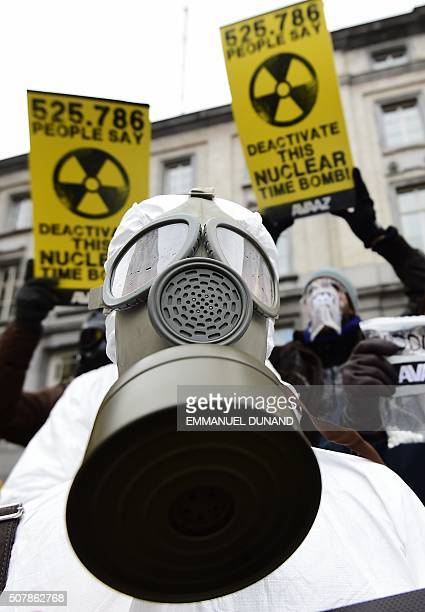 Antinuclear activists wearing gas masks and holding up placards reading '525 786 people say Deactivate this nuclear time bomb stage a protest against...
