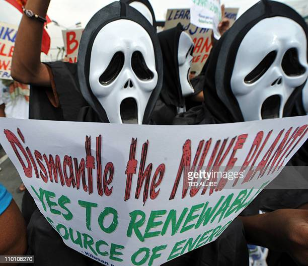 Antinuclear activists wearing masks hold a protest near the presidential palace in Manila on March 15 2011 as they rally against the revival of the...