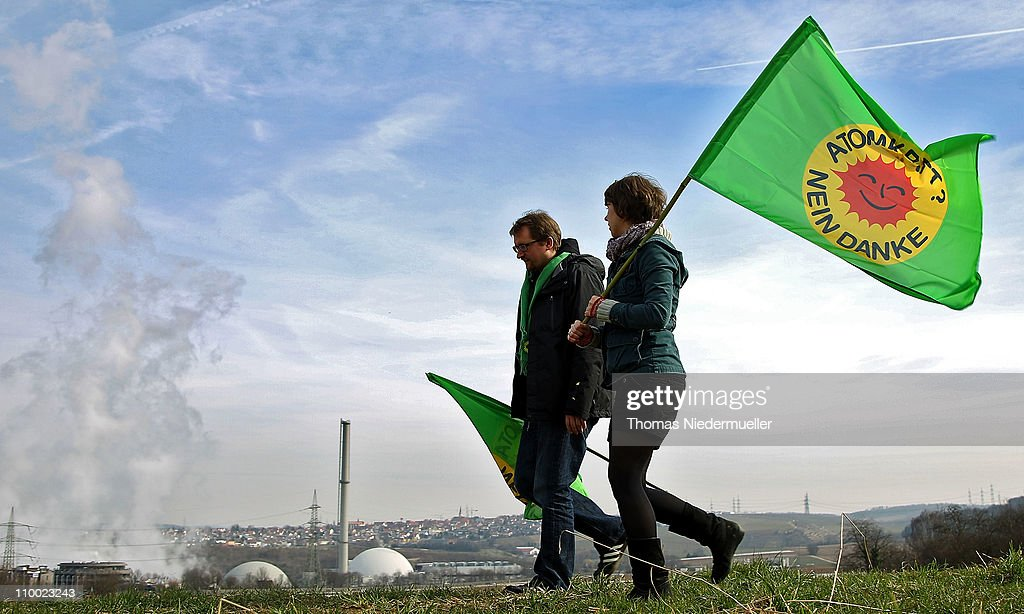 Anti-nuclear activists with flags walk in front of the Neckarwestheim nuclear power plant on March 12, 2011 near Neckarwestheim, Germany. The activists were protesting against the government-granted extension of the operational timespan of several of Germany's older nuclear power plants, which Chancellor Merkel's government claims is necessary to bridge demand before planned renewable energy projects begin operation. The activists claim their call for an end to nuclear power is all the more vital given the current, potential catastrophe brewing at at least one reactor at the tsunami-damaged Fukushima facility in Japan.
