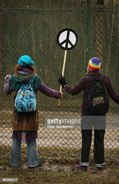 Antinuclear campaigners hold hands as they surround the perimeter fence at Aldermaston Atomic Weapons Establishment on March 24 2008 in Berkshire...