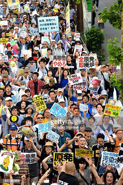 Antinuclear protesters carrying antinuke placards march through on October 13 2013 in Tokyo Japan With all the nation's 50 nuclear reactors offline...