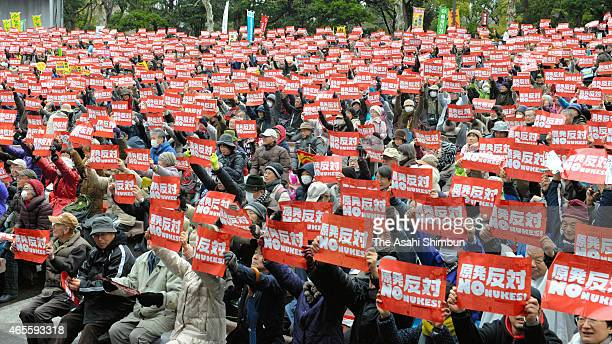 Antinuclear protesters hold banners to protest the restart of the nuclear plants during a rally at Hibiya Yagai Ongakudo Hall on March 8 2015 in...