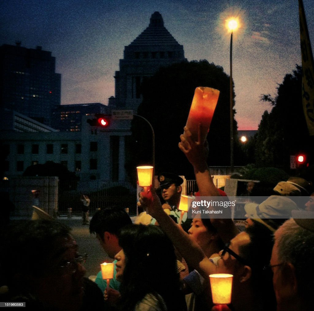 Anti-nuclear protesters hold candles during a mass demonstration outside the National Diet building on July 29, 2012 in Tokyo, Japan. Police have imposed tight controls on the weekly protest against restarting nuclear power plants. All 54 of Japan's nuclear plants had been offline for months, in the wake of the disaster at the Fukushima Daiichi nuclear plant. Protesters wanted the government to reconsider its energy policy but the government decided to restart the Ohi nuclear plant anyway.