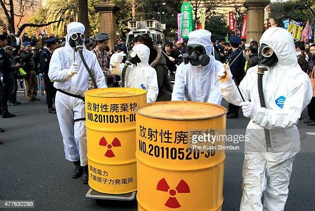 Antinuclear protesters wearing radiation protection gears rally in front of the Diet building on March 9 2014 in Tokyo Japan On March 11 Japan...