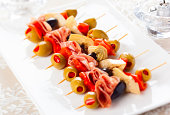 Antipasti skewers with olives,red pepper,artichoke hearts and salami for holiday