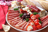 Platter of antipasto, with crusty bread.  A mixture of salami, prosciutto, bocconcini, grilled peppers stuffed with goat's cheese, eggplant, tomatoes, and olives. [url=file_closeup.php?id=7335664][img