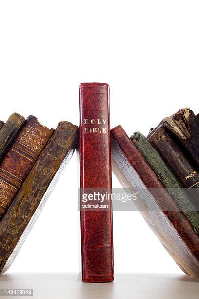 Antique Books Leaning On Holy Bible As Keystone