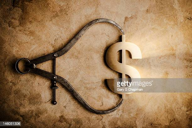 Antique calipers holding a dollar symbol