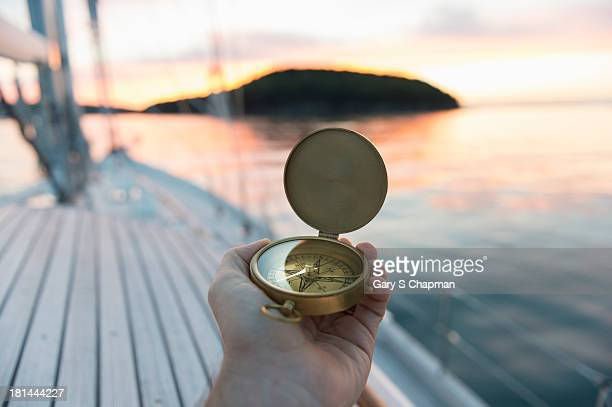 Antique compass at sunrise with sailboat