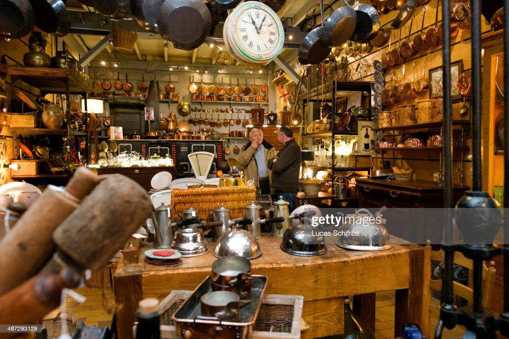 Antique dealer Francois Bachelier speaks with customer PaulHenri Goumet in his store is specialised in antique kitchen ustensils in SaintOuen flea...